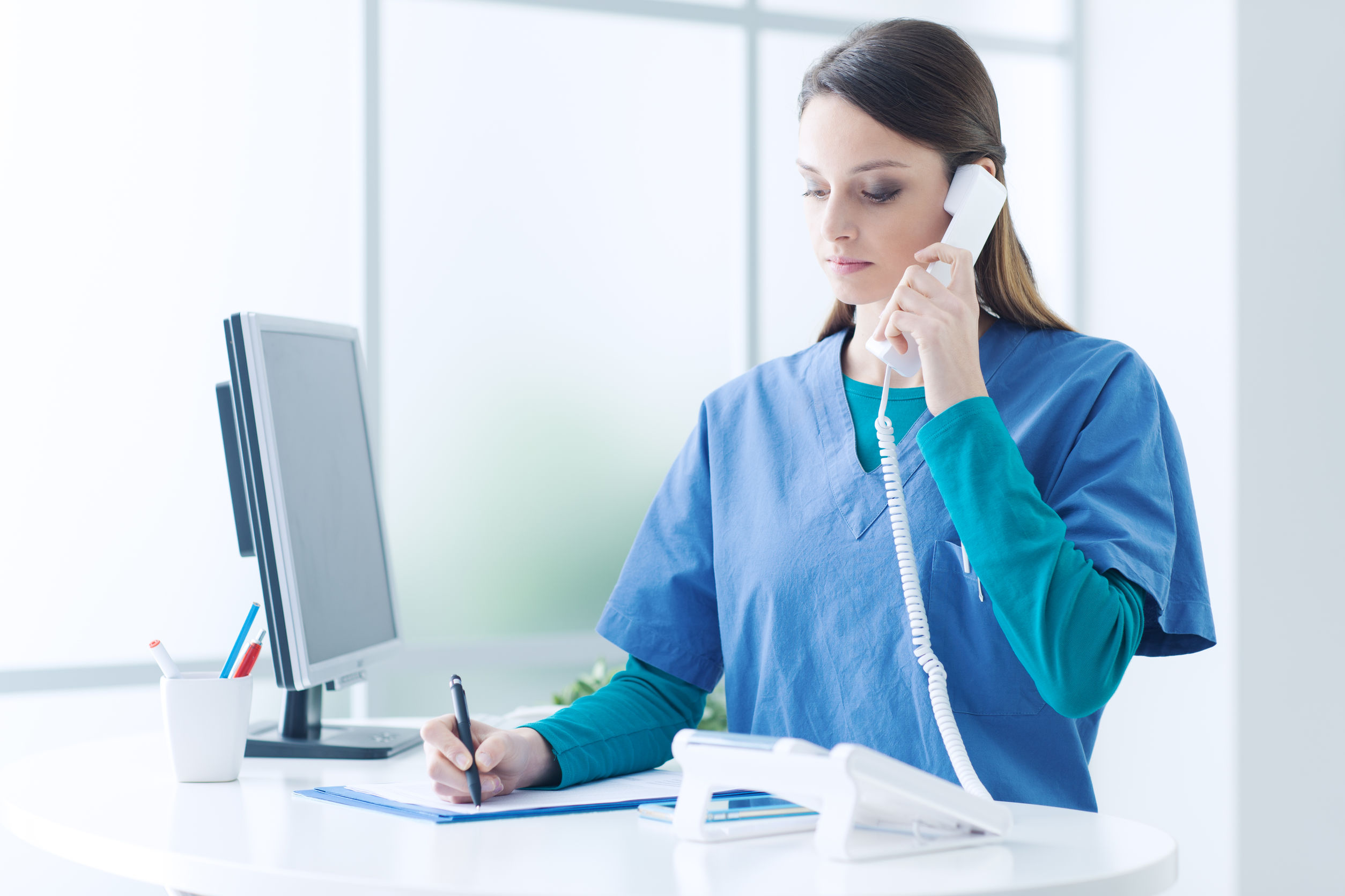 Young female doctor and practitioner working at the reception desk, she is answering phone calls and scheduling appointments