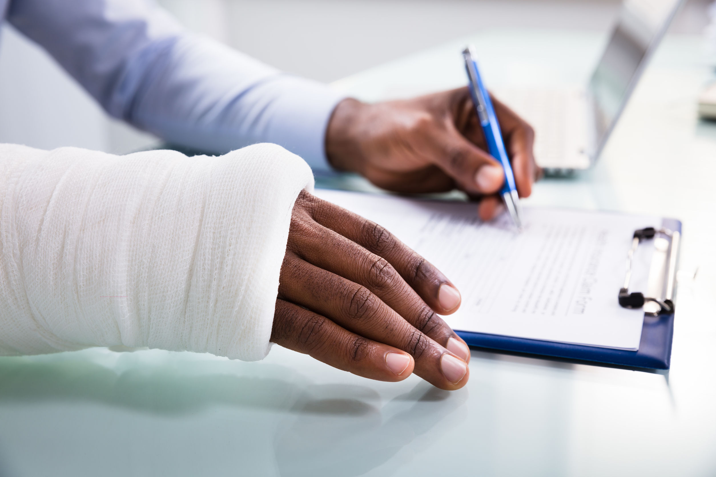 Overhead View Of Injured Man With Bandage Hand Filling Insurance Claim Form On Clipboard